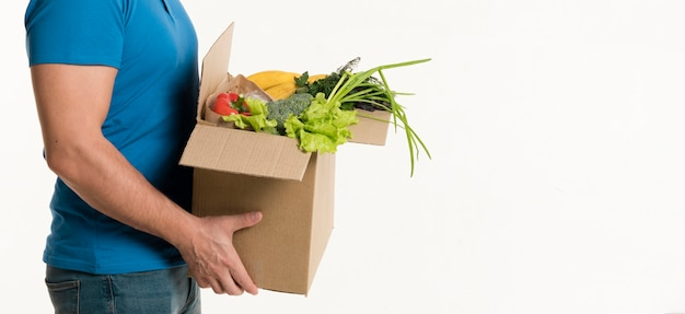 Side view of grocery box held by delivery man Free Photo
