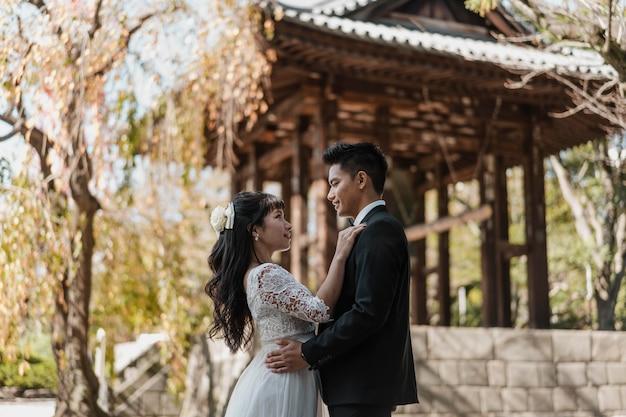 Vista laterale dello sposo e della sposa abbracciati all'aperto Foto Gratuite