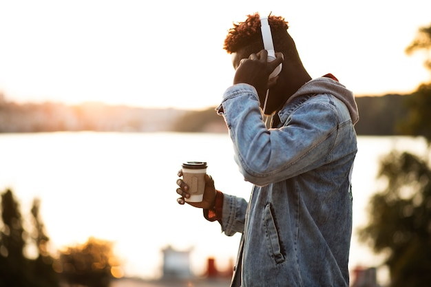 Side view guy with headphones and coffee cup Free Photo
