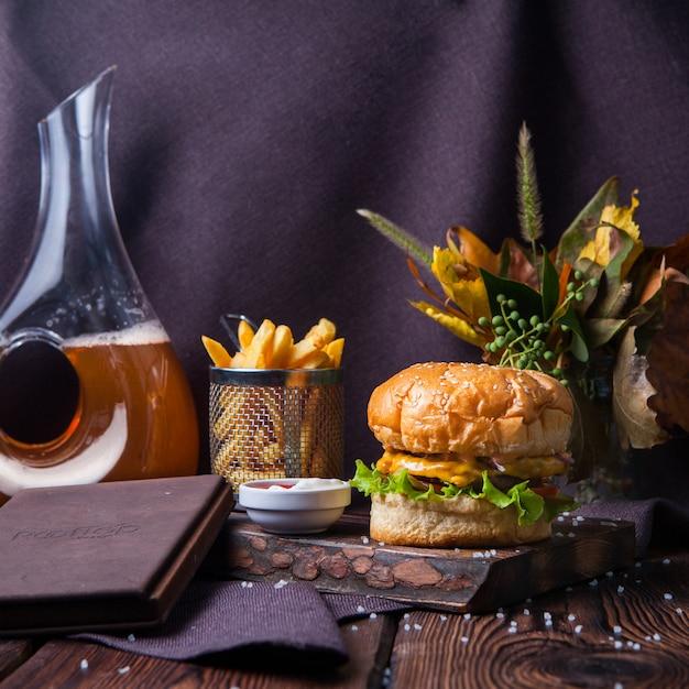 Вид сбоку гамбургер и картофель фри на дерево и черный фон с украшениями Бесплатные Фотографии