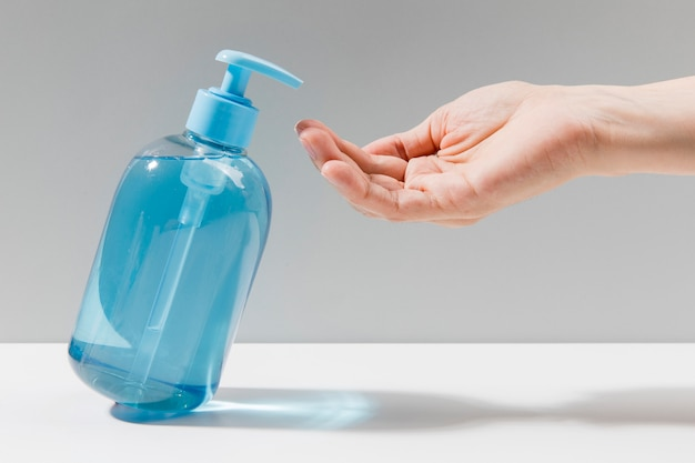 Side view of hand disinfection with hand sanitizer Premium Photo