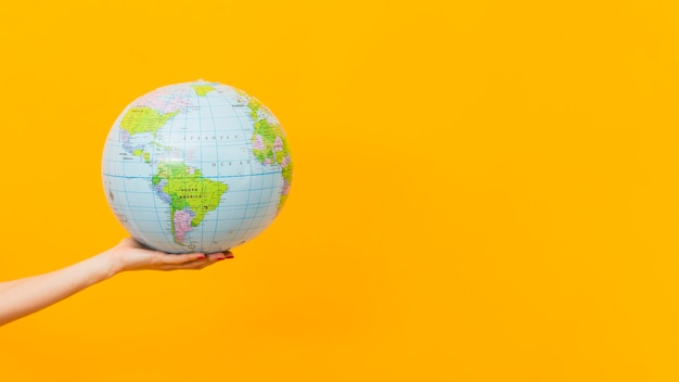 Side view of hand holding earth globe with copy space Free Photo