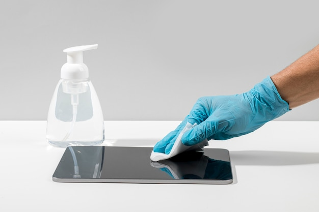 Side view of hand with surgical glove disinfecting tablet on desk Free Photo