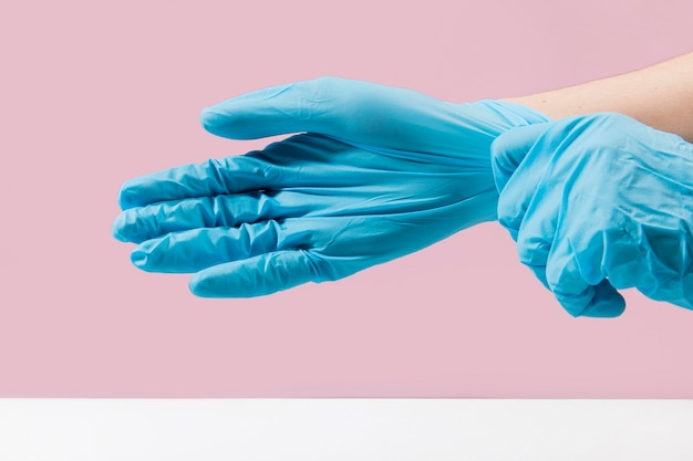 Side view of hands putting on surgical gloves Premium Photo