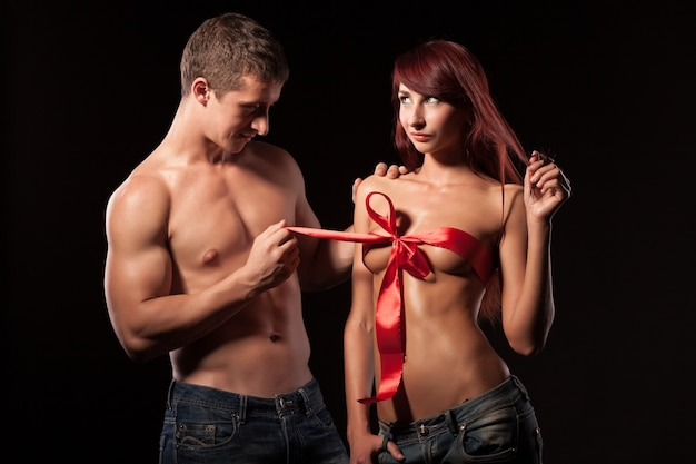 Side view of handsome man looking at naked girlfriend and pulling ribbon on lady breast. Premium Photo