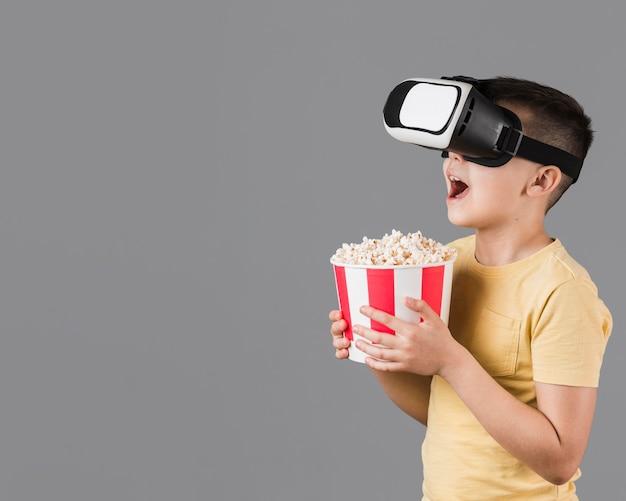 Vista laterale del ragazzo felice che tiene popcorn e indossando le cuffie da realtà virtuale Foto Gratuite