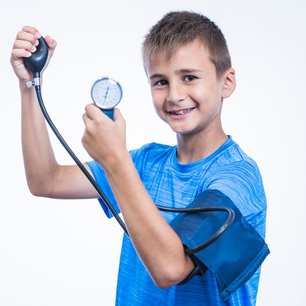 Side view of a happy boy measuring blood pressure on white background Free Photo