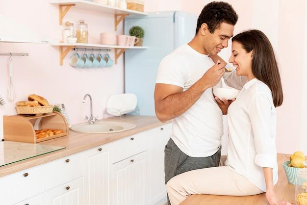 Coppie felici di vista laterale che mangiano nella cucina Foto Gratuite