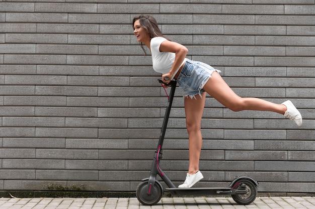 Vista laterale della donna felice in posa su scooter elettrico Foto Gratuite