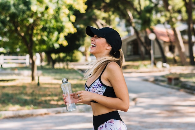 Side view of a happy young woman standing in the park holding water bottle Free Photo