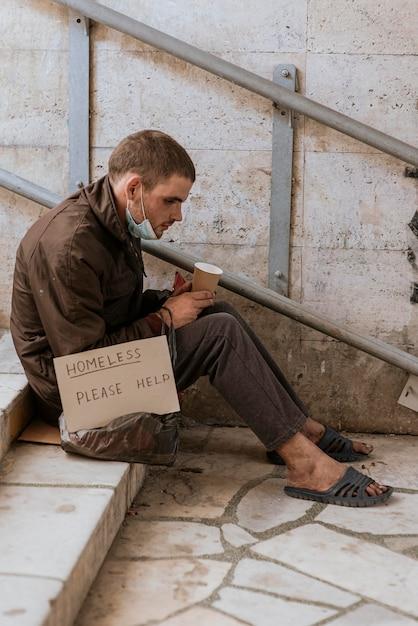 Vista laterale del senzatetto che tiene tazza e segno di aiuto Foto Gratuite