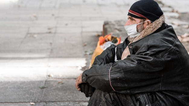 Side view of homeless man outdoors with cane and copy space Free Photo