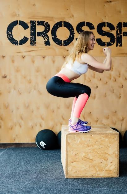 Immagine di vista laterale della giovane donna adatta che fa un esercizio di salto di scatola. donna muscolare che fa un box squat in palestra Foto Gratuite