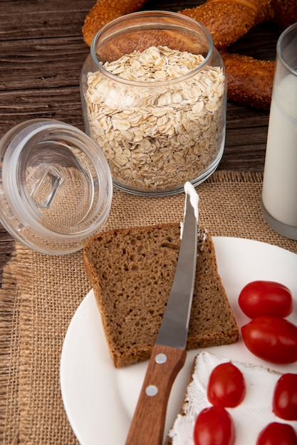 Side view of jar with oat-flakes and plate with rye bread slice tomatoes knife on sackcloth on wooden background Free Photo