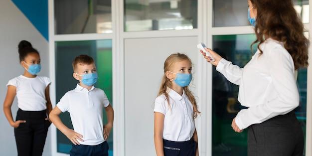 Vista laterale i bambini tornano a scuola in tempo di pandemia Foto Gratuite