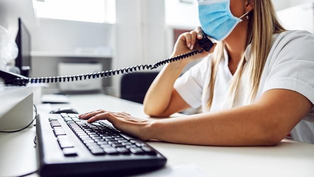 研究室に座って、covid-19陽性患者について緊急の電話をかけている、研究室のアシスタントの側面図。 Premium写真