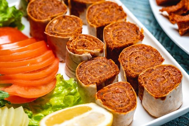 Вид сбоку рулет lahmacun с нарезанными листьями салата помидорами и ломтиком лимона на тарелке Бесплатные Фотографии