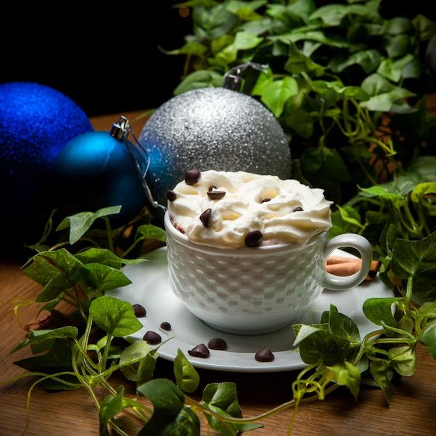 Латте с кофе в зернах и виноградной ветке и рождественский бал в чашке Бесплатные Фотографии