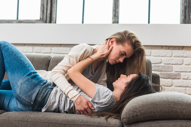 Side view of lesbian young couple lying on grey sofa looking at each other Free Photo
