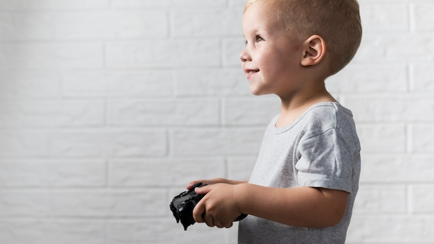 Side view little boy playing with a controller Free Photo