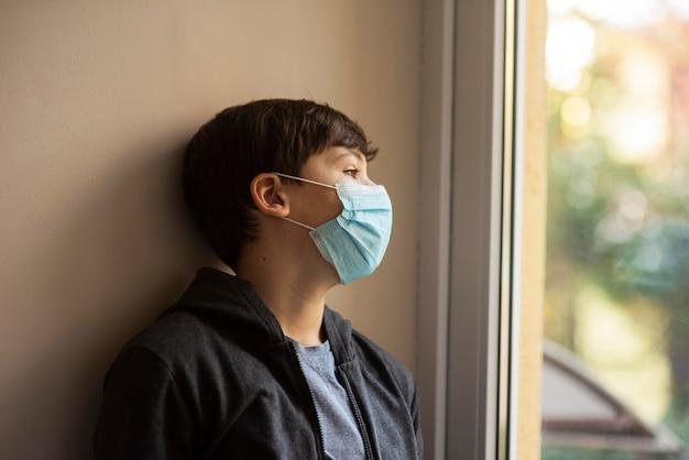 Ragazzino di vista laterale con mascherina medica che osserva via Foto Gratuite