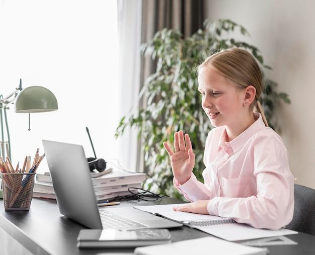 Вид сбоку маленькая девочка, участвующая в онлайн-классе Бесплатные Фотографии