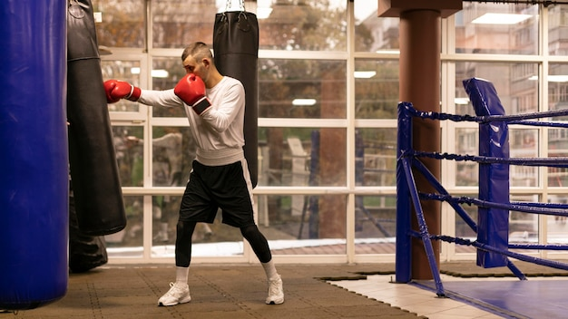 Side view of male boxer practicing with punching bag next to ring Premium Photo