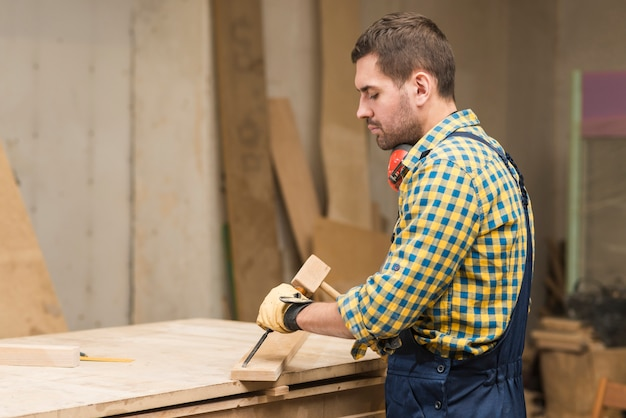 Side view of a male carpenter carving on wood with chisel in the workshop Free Photo