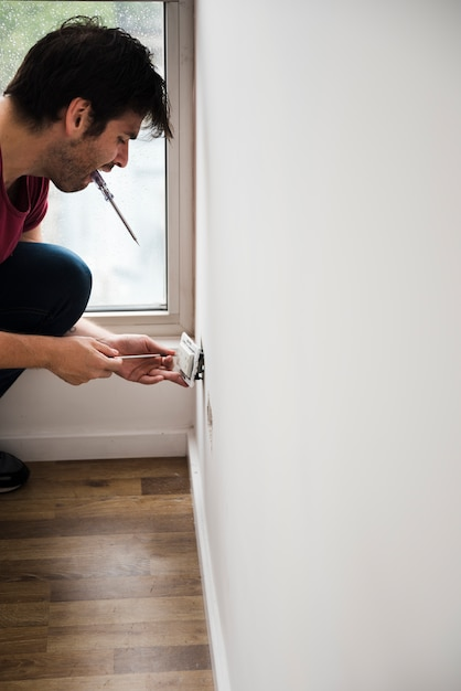 Side view of male electrician fixing plug on white wall Free Photo