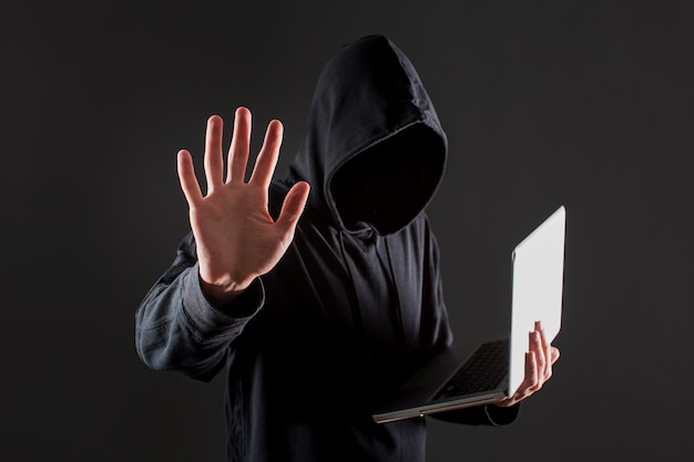 Side view of male hacker holding laptop and putting hand up as stop Free Photo