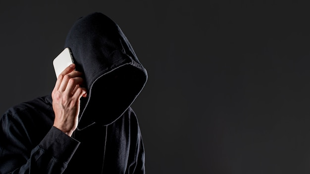 Side view of male hacker talking on smartphone with copy space Free Photo