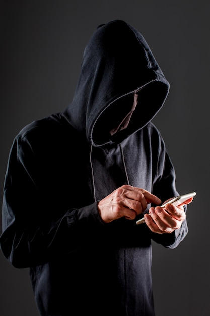 Side view of male hacker with smartphone Free Photo