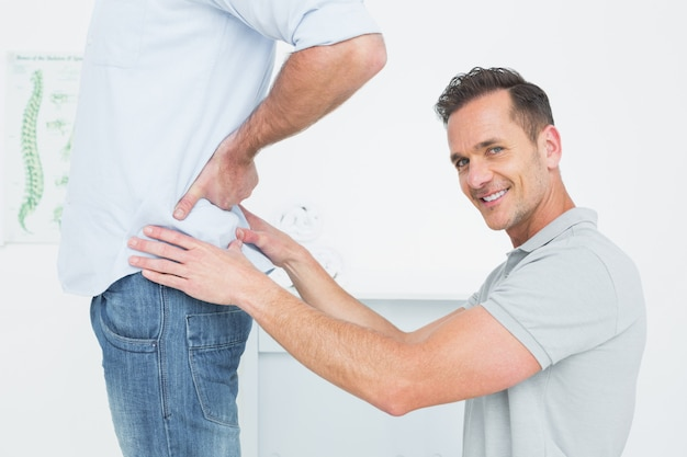 Side view of a male physiotherapist examining mans back Premium Photo