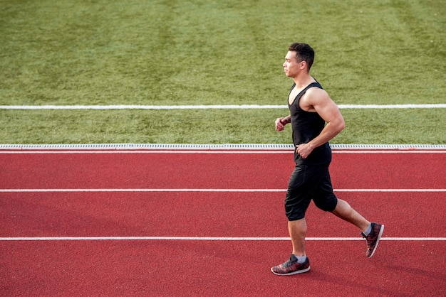 Side view of a male runner sprinter on race track running Free Photo