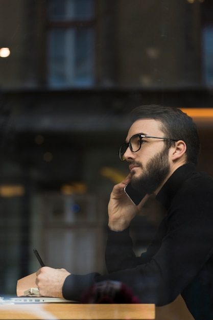 Side view male talking over phone Free Photo