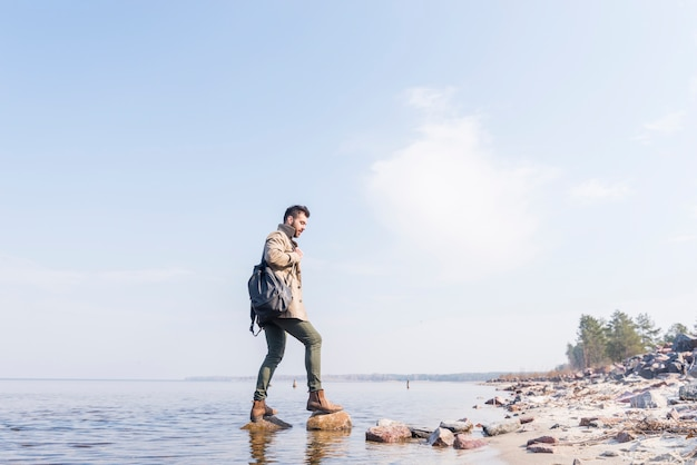 Side view of a male traveler with his backpack standing on the stones in the lake Free Photo