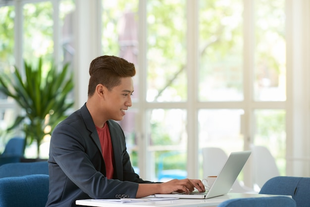 Side view of man busy typing on laptop keyboard with a smile Free Photo