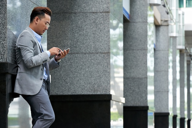 Side view of man checking smartphone at the lunch break outdoors Free Photo