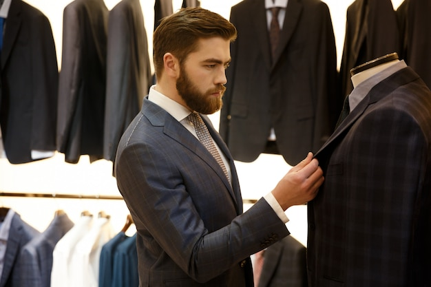 Side view of man choosing a jacket in shop Free Photo
