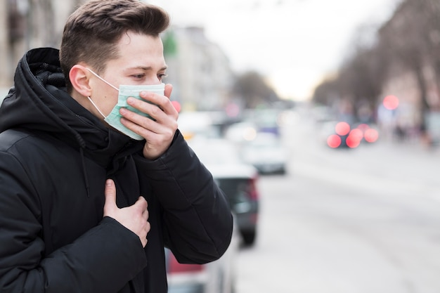 Side view of man in city coughing while wearing a medical mask Free Photo
