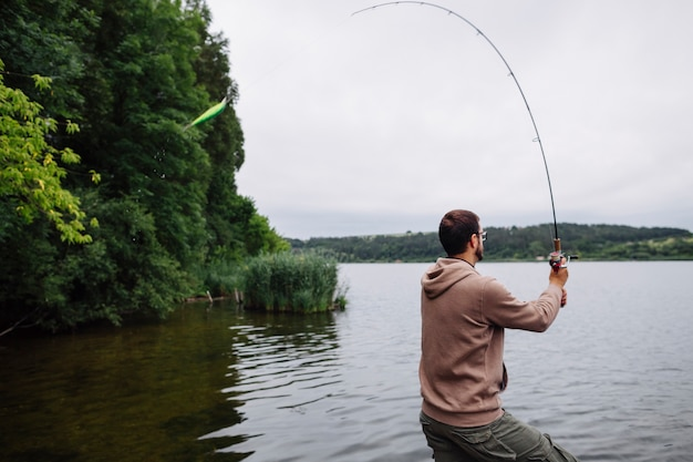 Side view of man fishing in the lake Free Photo