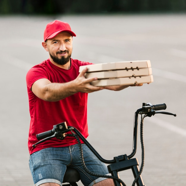 Side view man holding up pizza boxes Free Photo
