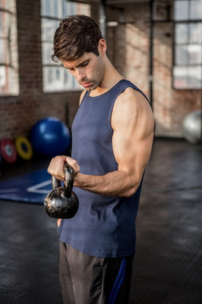 Side view of a man lifting kettlebell Premium Photo