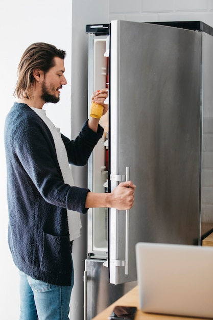 Side view of a man looking at juice bottle taken from the refrigerator at home Free Photo