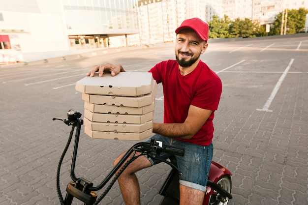 Side view man on motorcycle holding pizza boxes Free Photo