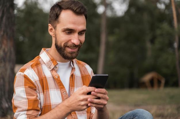 Vista laterale dell'uomo all'aperto guardando smartphone Foto Gratuite
