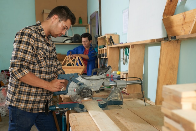 Side view of man in plaid shirt sawing wood in the timber workshop Free Photo