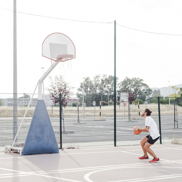 Side view of a man preparing to throw basketball in hoop Free Photo