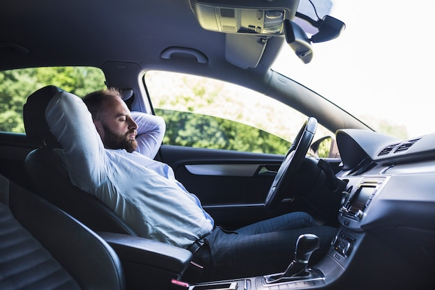 Side view of a man relaxing in car Free Photo