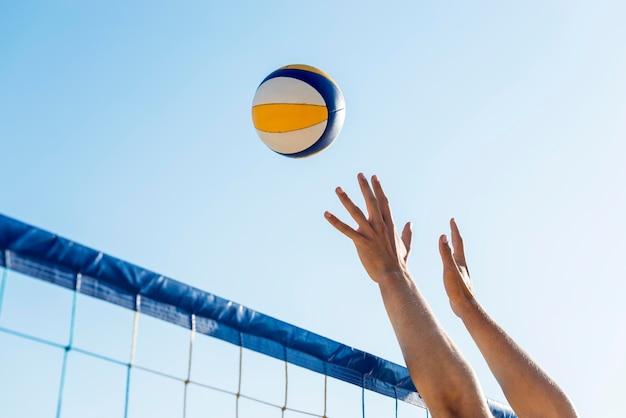 Vista laterale delle mani dell'uomo che si preparano a colpire la pallavolo in arrivo sopra la rete Foto Gratuite